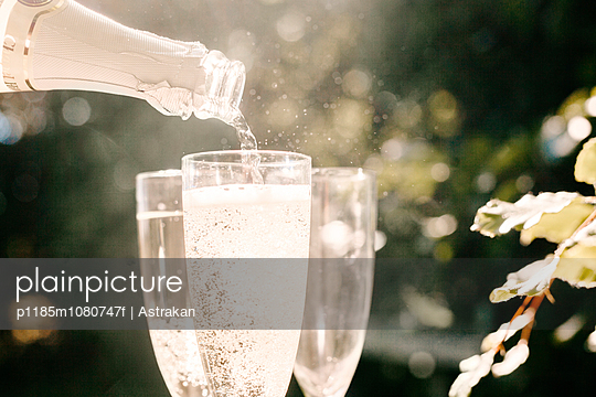 Champagne being poured in glass at graduation party