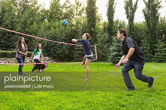 Father playing volleyball in the backyard with his daughters; Sherwood Park, Alberta, Canada