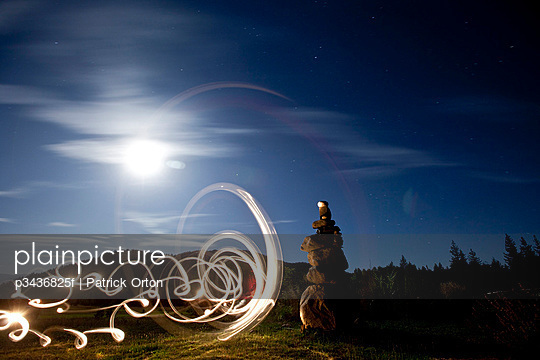 Rock cairn with light painting next to it and full moon in background in Idaho