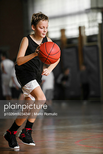 Boy playing basketball in a hall
