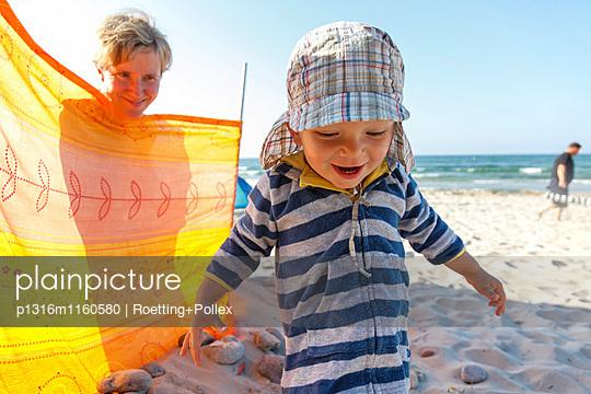 Junge spielt am Strand, Mutter hinter Windschutz, Bakenberg, Halbinsel Wittow, Insel Rügen, Mecklenburg-Vorpommern, Deutschland - p1316m1160580 von Roetting+Pollex