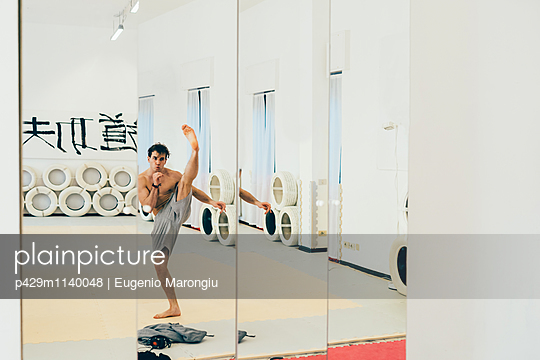 Mirror image of martial artist in gym doing kick