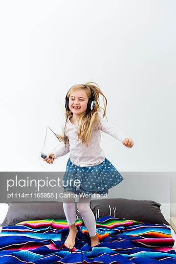 Mädchen springt auf dem Bett und hört Musik - p1114m1165958 von Carina Wendland