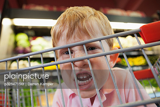 Close up of boy (5-6) making faces behind shopping cart
