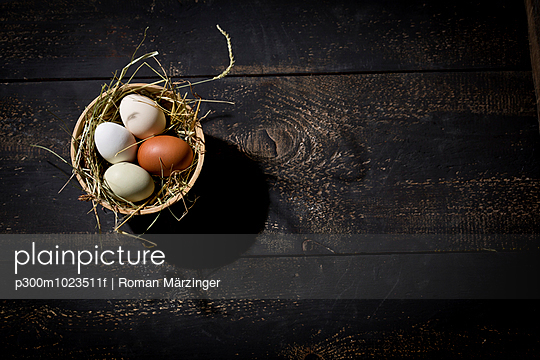 Easter nest with eggs in bowl on dark wood