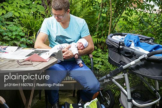 Vater hält Neugeborenes auf dem Arm und liest Zeitung, Leipzig, Sachsen, Deutschland - p1316m1160763 von Roetting+Pollex