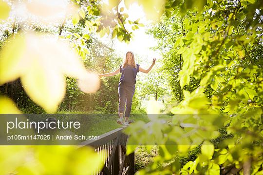 Junge Frau balanciert auf einem Geländer  - p105m1147025 von André Schuster