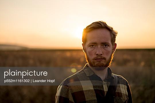 Junger Mann bei Sonnenuntergang - p552m1161302 von Leander Hopf