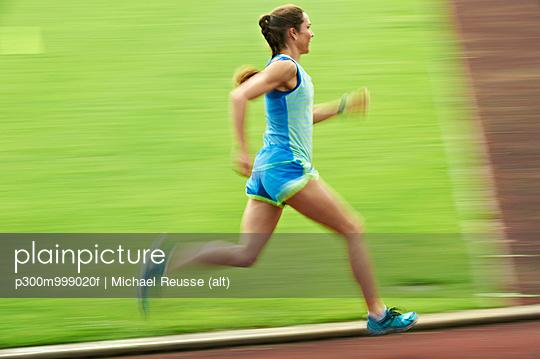Woman running on tartan track