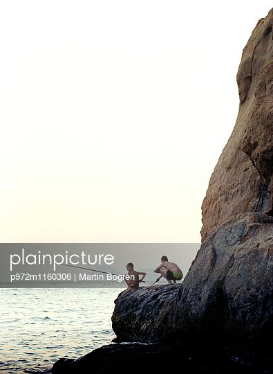 Zwei Jungen fischen an der Felsküste - p972m1160306 von Martin Bogren