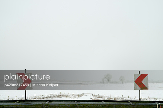 Road signs in snowy rural landscape
