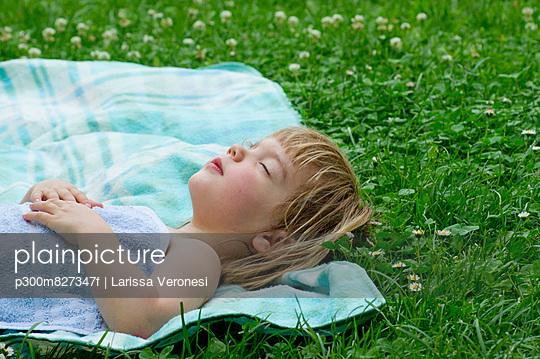 Girl sleeping on picnic blanket in meadow