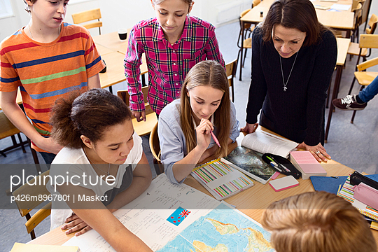 High angle view of teacher and students studying map at desk in classroom