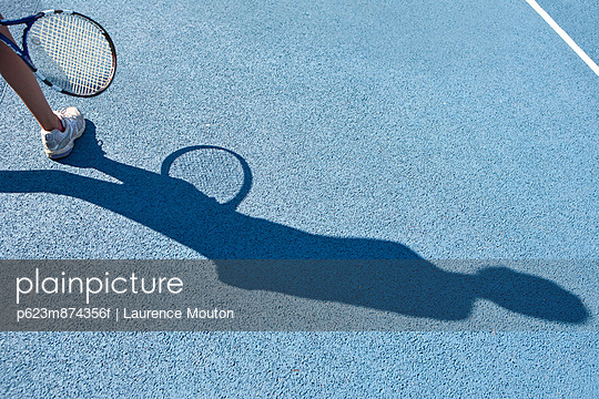 Tennis player standing in tennis court, focus on shadow