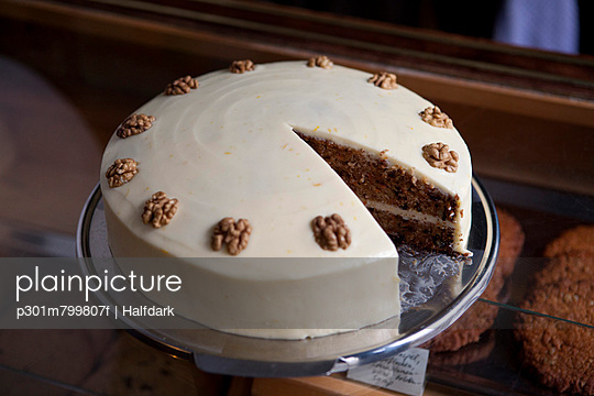 A carrot cake on a display cabinet in a cage with a piece missing