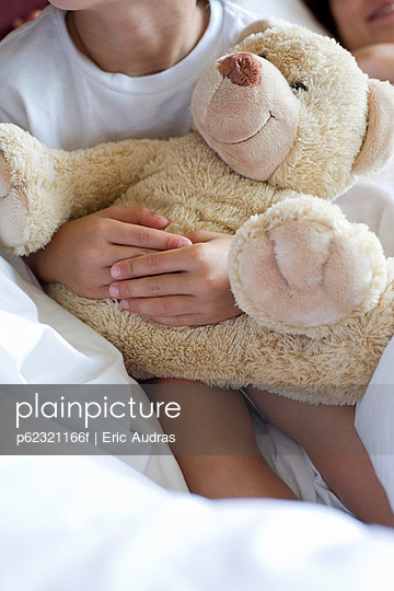 Child hugging teddy bear, cropped