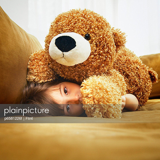 Girl Hiding Under Teddy Bear