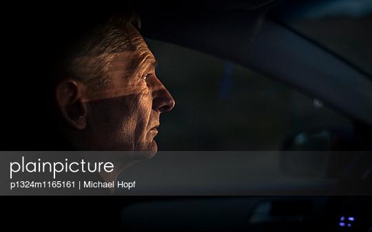 Reifer Mann fährt nachts mit dem Auto - p1324m1165161 von michaelhopf