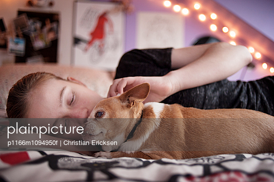 Girl with Chihuahua relaxing on bed at home