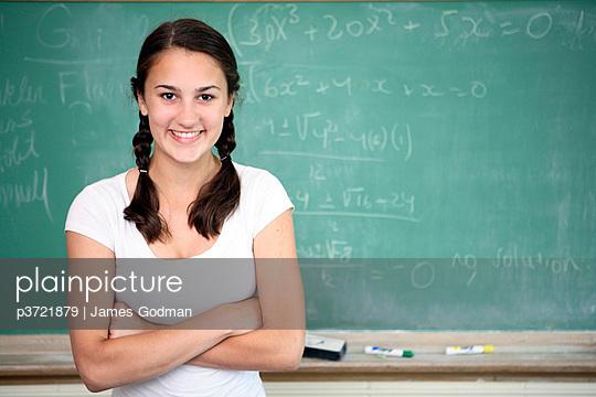 Portrait of teen girl in front of chalkboard
