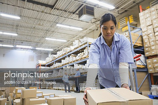 Female worker moving boxes in warehouse