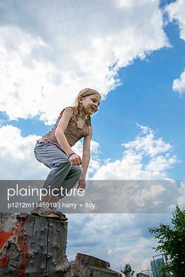 Mädchen springt vom Baumstumpf - p1212m1145910 von harry + lidy