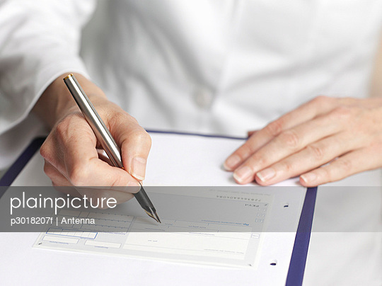 Human hands filling out medical paperwork