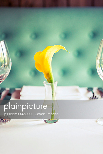 Yellow flower in vase on dining table at restaurant