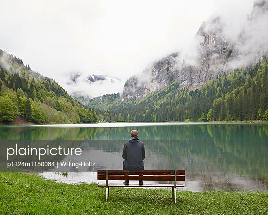 Mann sitzt auf Bank am Lac de Montriond - p1124m1150084 von Willing-Holtz