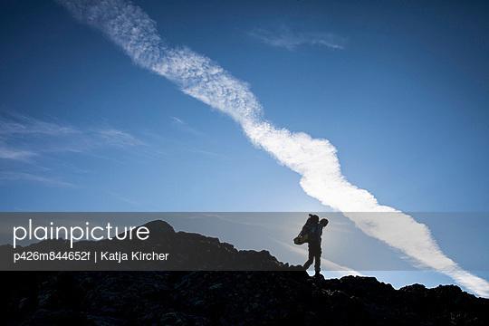 Silhouette of female hiker walking on rocks against sky
