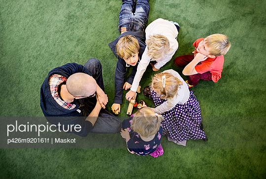 Directly above shot of teacher with students playing on rug in kindergarten