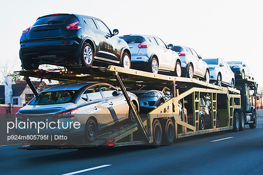 Cars transported on truck on highway