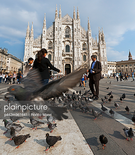 Milan Cathedral with people feeding birds in the foreground; Milano, Italy