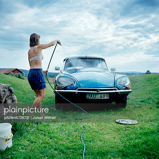 Woman washing vintage car