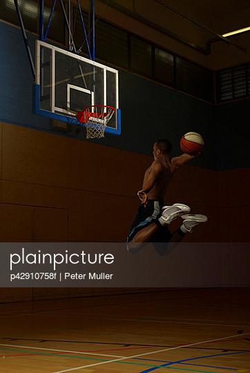 Basketball player jumping at goal hoop