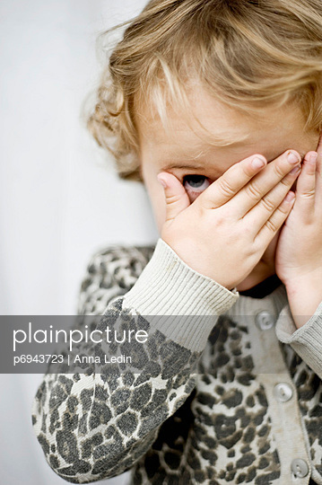 Young Child Covering Eyes With Hands and Peeking Though Fingers