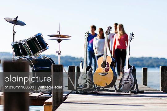 Musikinstrumente auf einem Steg am Starnberger See, vier Personen im Hintergrund, Bayern, Deutschland - p1316m1160609 von Wilfried Feder