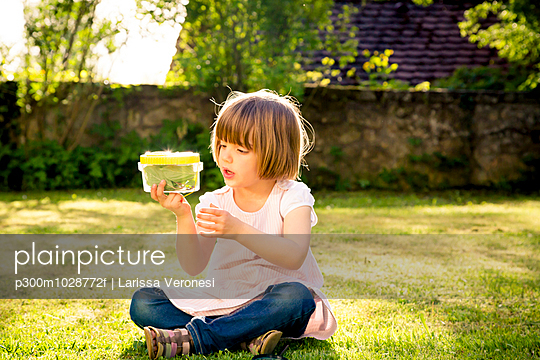 Little girl with insect can sitting on a meadow