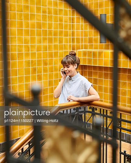 Junge Frau telefoniert im Treppenhaus - p1124m1150227 von Willing-Holtz