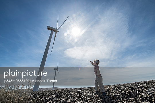 A young boy points up to a wind turbine with the sun in the background.