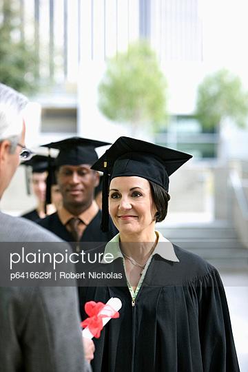 Dean presenting graduates with diplomas