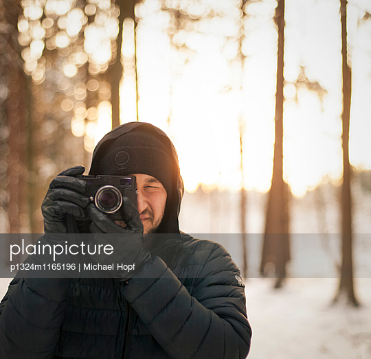 Junger Mann in Winterkleidung mit Fotoapparat - p1324m1165196 von michaelhopf