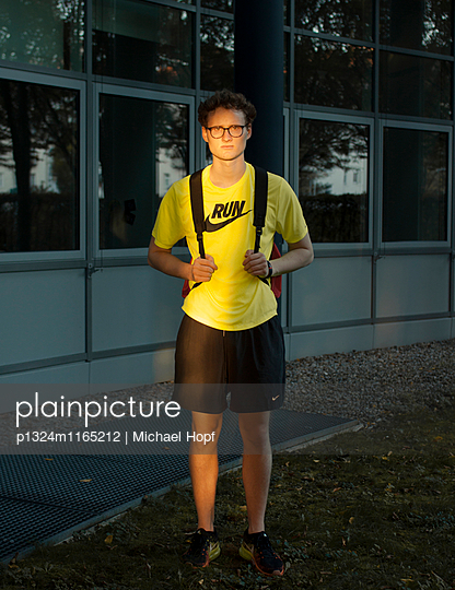 Junger Mann mit Rucksack im gelben Shirt - p1324m1165212 von michaelhopf
