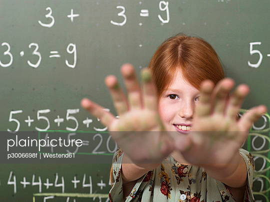 Girl (6-9) standing by black board with arms out, portrait