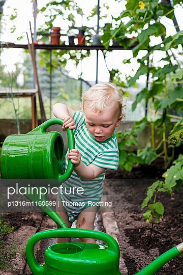 Junge mit einer Gießkanne in einem Gewächshaus, Freital, Sachsen, Deutschland - p1316m1160599 von Thomas Roetting