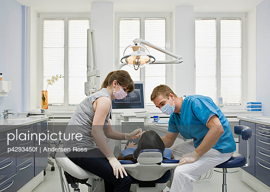 Dentist with patient and assistant