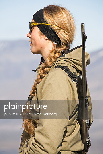 A young woman on a hiking tour in the mountains, Svalbard, Norway.