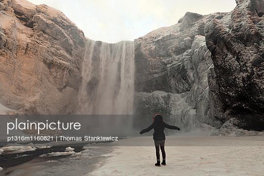 Frau am Skogar Wasserfall an der Küste unter dem Porsmörk, Südisland im Winter, Island - p1316m1160821 von Thomas Stankiewicz