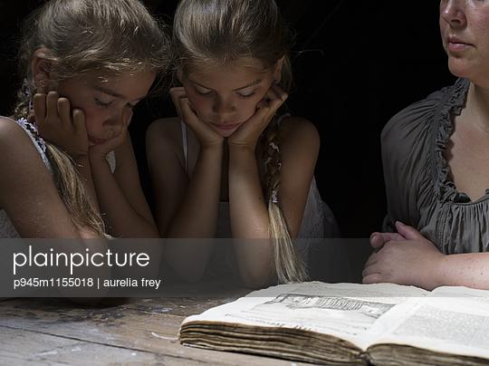 Mutter mit ihren zwei Töchtern beim Lesen - p945m1155018 von aurelia frey