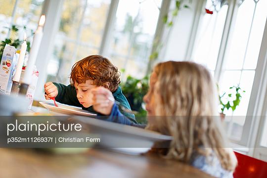 Sweden, Boy (6-7) and girl (10-11) eating breakfast